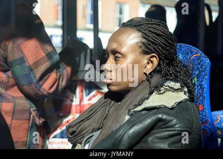 Sleepy black woman with dreadlocks hair sitting on a bus in bright sunshine - Stock Photo