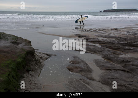 Male surfer in wet suit walks along rocky waters edge carrying surf board - Stock Photo