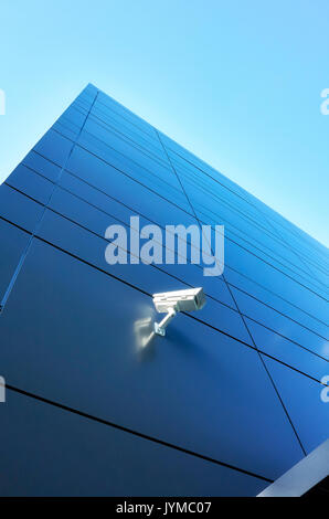 Closed circuit television (CCTV) camera on an office building wall. - Stock Photo