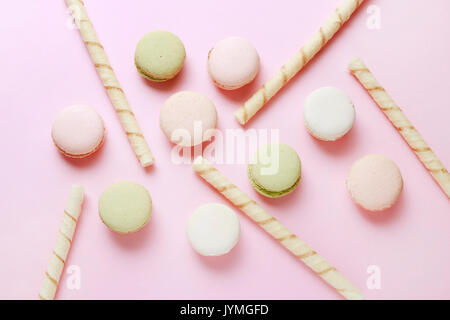 French macaroons and crispy wafer rolls on pink background. - Stock Photo