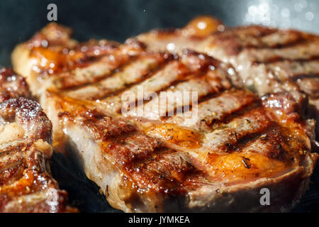 Raw Ribeye Steak with Herbs and Spices, frying on grill pan.