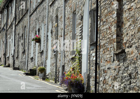 a row of old stone built 19th century workers cottages in Cornwall facing directly onto the street with hanging - Stock Photo