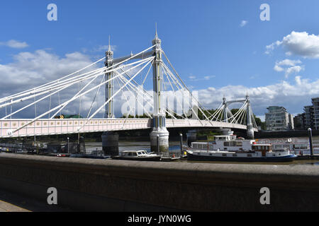 London: Albert Bridge in Chelsea on a sunny day. From the north bank of the Thames looking south to Battersea. - Stock Photo