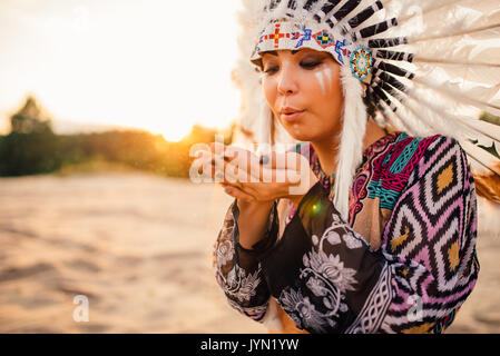 Female American Indian play with sand on sunset. Young girl in headdress made of feathers of wild birds. Traditional - Stock Photo