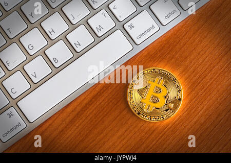 Gold Bitcoin coin on wooden table near modern keyboard - Stock Photo