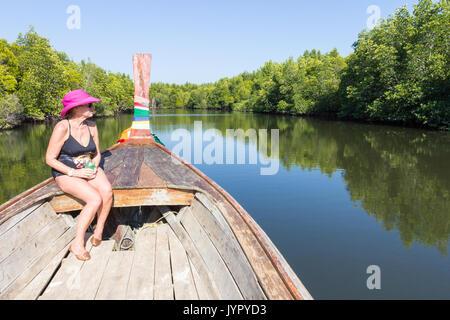 Senior woman sat in prow of boat sailing through the mangrove, Kho Libong, Trang, Thailand - Stock Photo