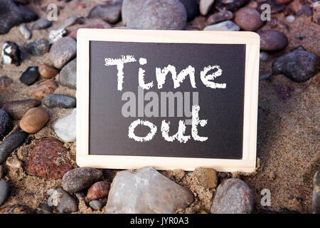blackboard lying between stones on a sandy beach with the words Time Out - Stock Photo