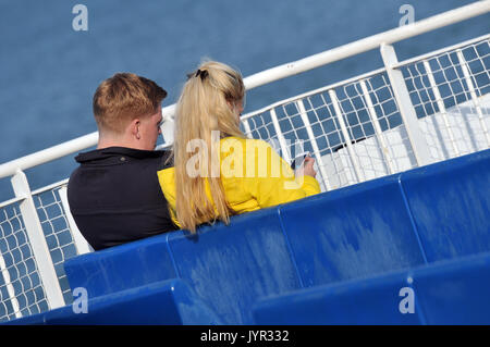 a young couple using mobile phones or devices sharing messages looking at screens romantic arm in arm on a ferry - Stock Photo