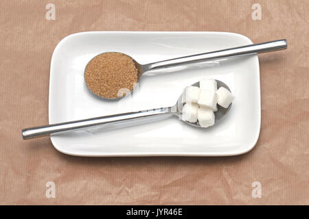 Sugar food staples with white cubes and brown sugar in spoons on white plate - Stock Photo