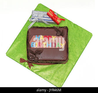Chocolate birthday cake with colorful sign and presents on the side - Stock Photo