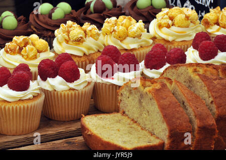 Some gluten free sticky cream and iced icing cakes on display on a cake stand sweet sugary produce for sale very - Stock Photo