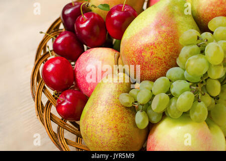 Fruit harvest. Organic fresh apples, pears, grapes and plums in a woven wooden plate - Stock Photo