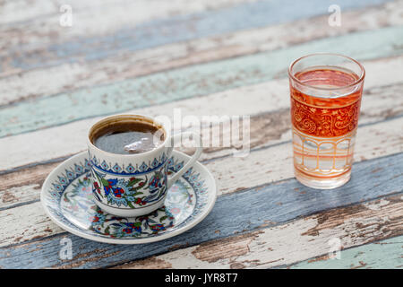 Turkish coffee in traditional cup with glass of water on vintage table - Stock Photo