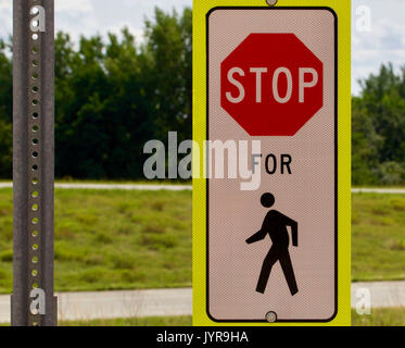 Stop for pedestrian sign against a green background - Stock Photo