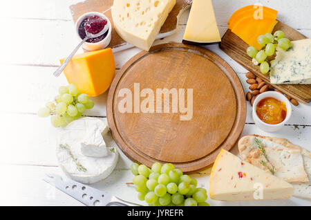 Assorted cheeses served with grapes, jam,  bread and nuts on a wooden background. - Stock Photo