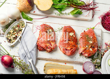 Marinated pork steaks on cutting board and fresh vegetables for healthy eating. - Stock Photo