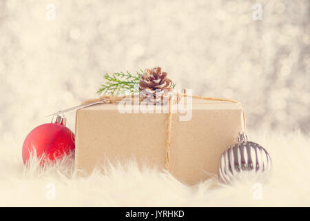 Brown paper craft warped on present box decorate with pine cone and green leaf christmas ball at sparkling bokeh - Stock Photo