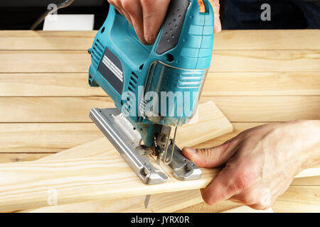 man carpenter builder working with electric jigsaw and wood, on wooden table - Stock Photo