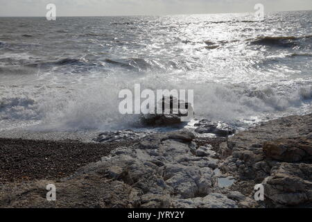 Waves crashing in on the incoming tide on the coastline in Wales with the sun reflected on the rippling waters - Stock Photo