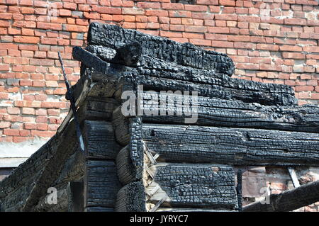 Close-up view of a charry corner of a burnt wooden house against a red brick wall. - Stock Photo