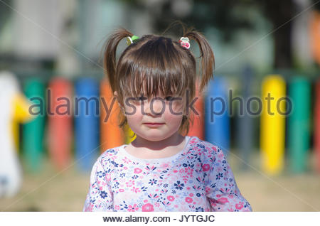 Cute portrait of a little girl with pigtails looking and smiling at the camera with a expression - Stock Photo