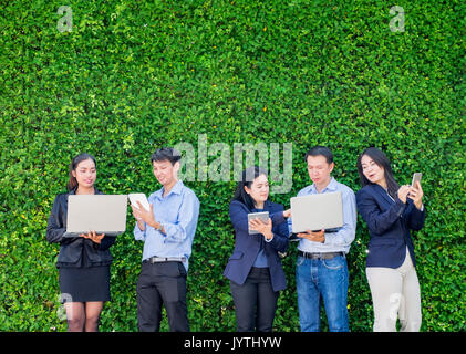 Businesswoman and businessman working outside office using laptop computer mobile phone and tablet device at green - Stock Photo