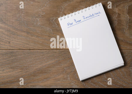 new year resolutions tempate with notepad on wood table - Stock Photo