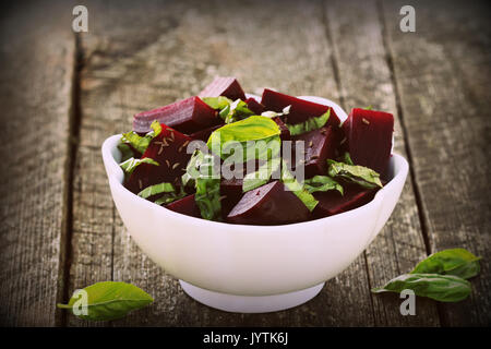 Beetroot chopped for salad with basil and dill seeds in bowl on rustic wooden table - Stock Photo