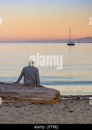A gray haired man in a beige jacket seated on driftwood looking at the sailboats on the ocean at sunset. - Stock Photo
