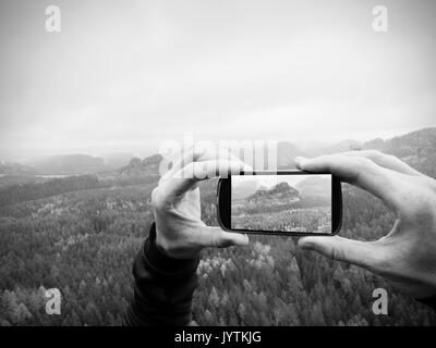 Smart phone mobile photography of misty spring mountains landscape. Focus to detail with phone in man hands. Long - Stock Photo