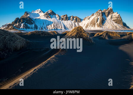 Stokksnes, Eastern Iceland, Europe. Small mounds in with Vestrahorn mountain in the backdrop in a frozen winter - Stock Photo