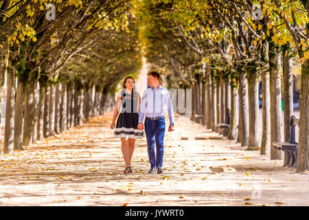 Couple walk holding hands in between rows of trees in the Jardin du Palais Royal in Paris - Stock Photo