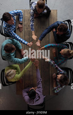 Modern business meeting concept, people in casual clothes sitting around wooden table giving high five - Stock Photo
