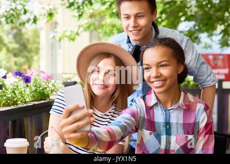 Teenage Friends Taking Selfie in Cafe - Stock Photo