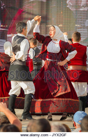 Cavalcata Sassari, a couple dressed in traditional costume perform a folk dance during the Cavalcata Sarda festival - Stock Photo