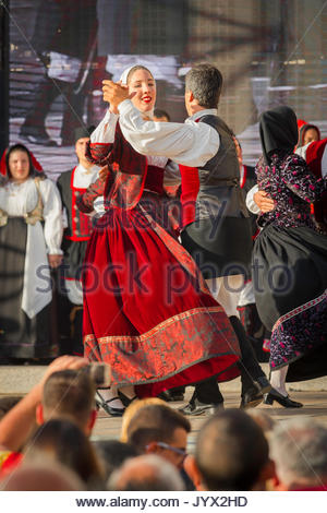 Festival Sardinia, a couple dressed in traditional costume perform a folk dance during the Cavalcata Sarda festival - Stock Photo