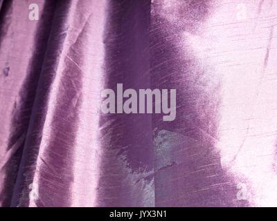 purple curtain detail texture fabric cloth shiny sheen; England; UK - Stock Photo