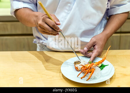 Chef preparing and cooking lobster sashimi - Stock Photo