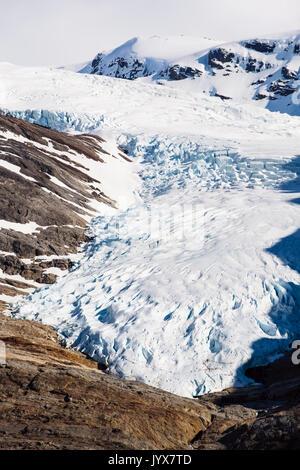 Engabreen or Enga glacier arm of Svartisen ice cap with people walking on rocks to show scale. Saltfjellet-Svartisen - Stock Photo