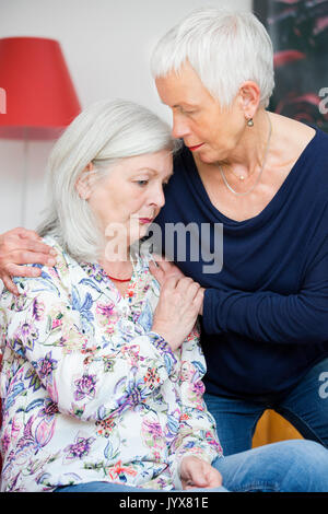 Older woman comforts her friend - Stock Photo
