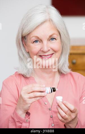 Older woman takes globules - Stock Photo