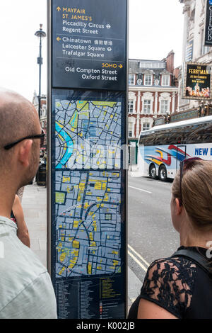 Two people looking at a tourist information sign outside the Gielgud Theatre Shaftesbury Avenue London, England - Stock Photo