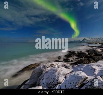 Northern lights on the cold sea of  Gymsøyand where the waves break on the rocks. Lofoten Islands Northern Norway - Stock Photo
