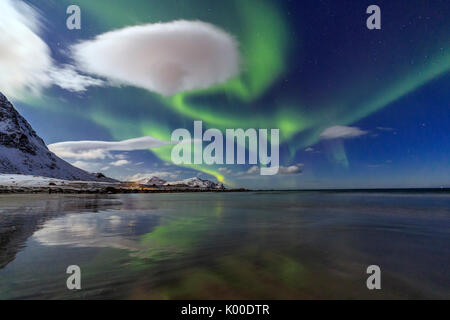 Northern Lights illuminate the landscape around Skagsanden and the snowy peaks. Lofoten Islands Northern Norway - Stock Photo
