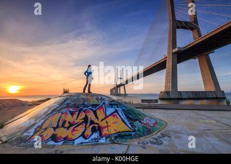 A tourist admires the majestic Vasco da Gama Bridge over the River Tagus Parque das Nações Lisbon Portugal Europe - Stock Photo