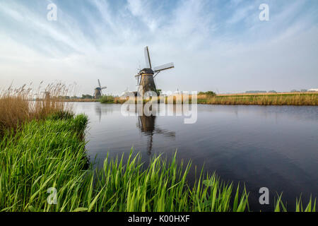 Green grass frames the windmills reflected in the canal Kinderdijk Rotterdam South Holland Netherlands Europe - Stock Photo