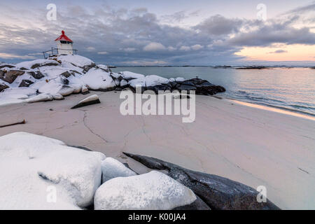Colorful arctic sunset on the lighthouse surrounded by snow and icy sand Eggum Vestvagoy Island Lofoten Islands - Stock Photo