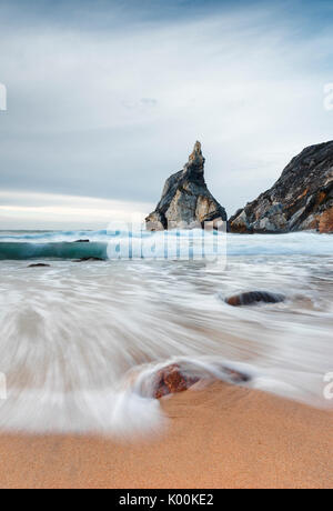 Ocean waves crashing on the sandy beach of Praia da Ursa surrounded by cliffs Cabo da Roca Colares Sintra Portugal - Stock Photo