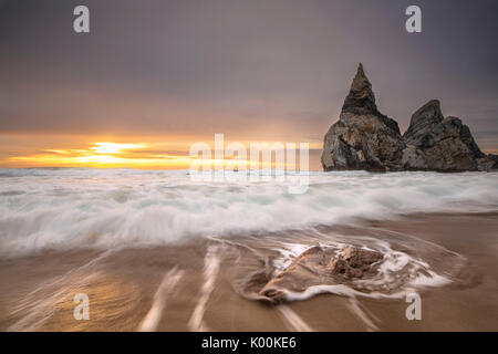 Ocean waves crashing on the beach of Praia da Ursa at sunset surrounded by cliffs Cabo da Roca Colares Sintra Portugal - Stock Photo