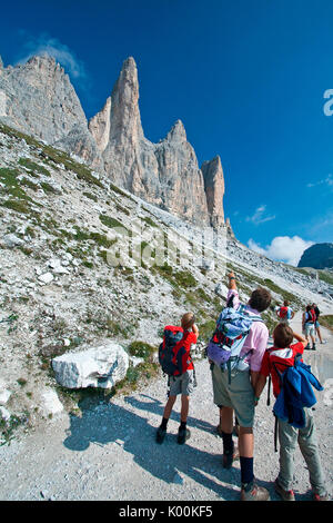 Hikers watch the bold peaks of the Three Peaks from the path that leads to the Lavaredo Refuge. Auronzo of Cadore. - Stock Photo